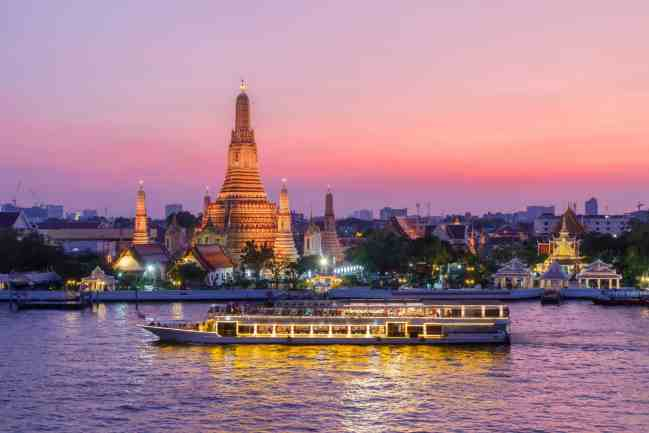 The vibrant glow of Wat Arun in the early evening, along the banks of Bangkok's, Chao Phraya River.