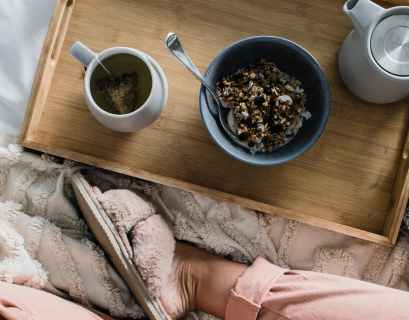 woman sitting on bed with breakfast on tray