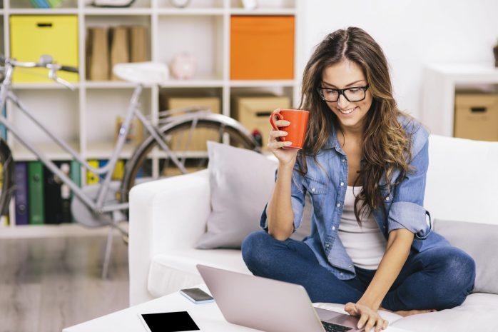 Femme assise dans un canapé regardant un laptop