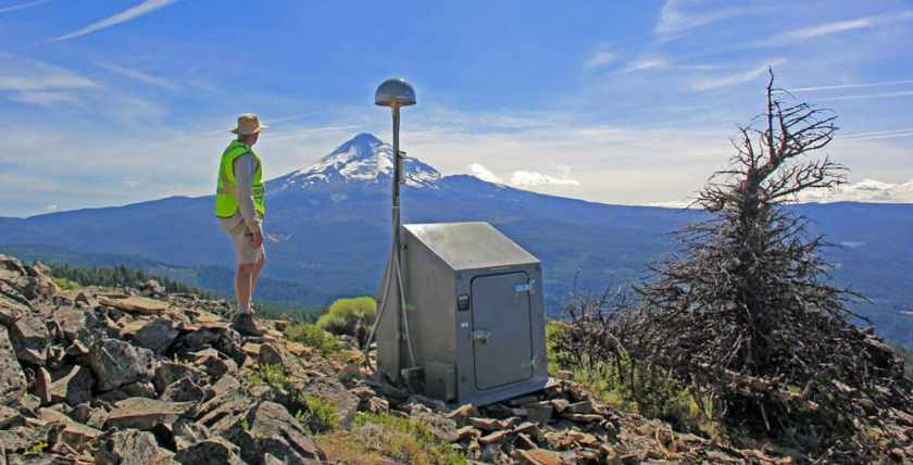 This station contains a combined GPS and seismometer.  Photo: USGS geologist viewing the northeastern slope of Mount Hood from Shellrock monitoring station, Liz Westby, USGS Cascades Volcano Observatory. Public domain, July 16, 2015.