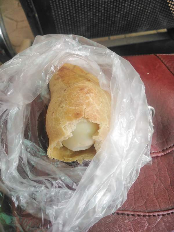 Lady in shock after finding whole boiled egg inside meat pie