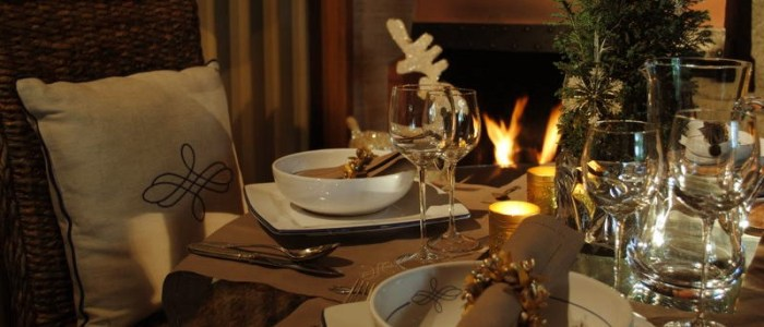 Christmastime by the fireplace, handmade embroidered place mats, elegant ceramics setting