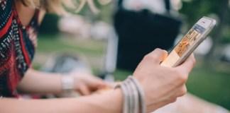 foto de mujer con móvil en la mano revisando por qué su móvil se calienta y se apaga