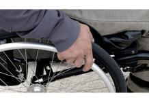 foto de una mano que gira una rueda de una silla de ruedas