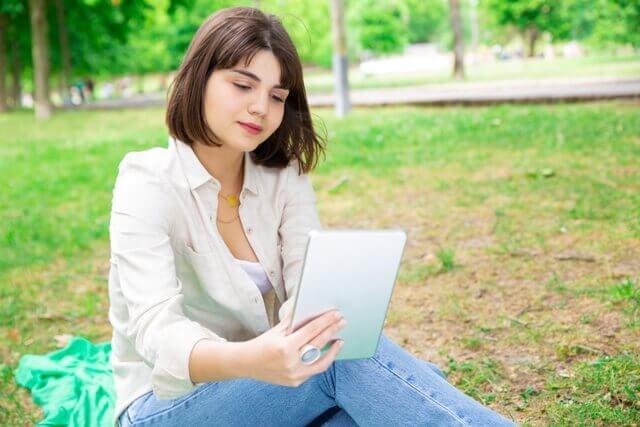 mujer leyendo una tablet en un parque