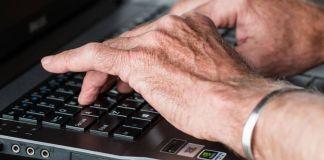 Imagen de las manos de un adulto mayor escribiendo sobre un teclado