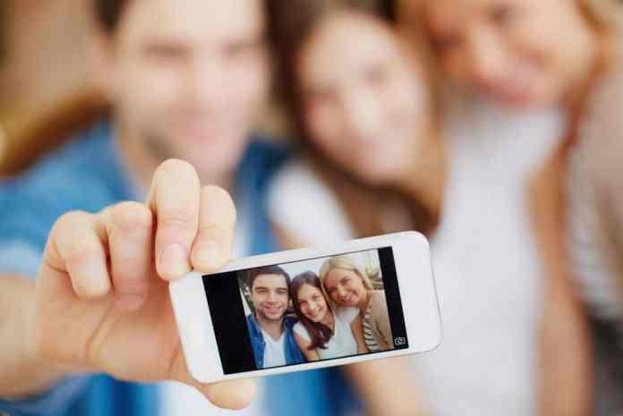 Fotografía de padres tomándose una selfie con su hija