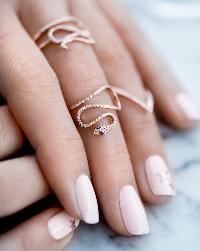 Neutral nail colors and rose gold jewelry on hand model and fashion blogger