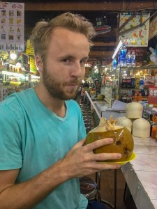 Backpacker drinking fresh coconut at a street market in Saigon, Vietnam