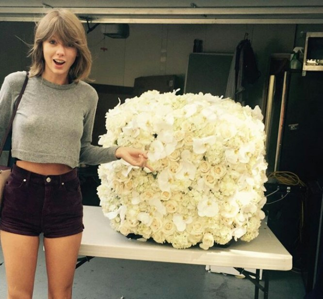 Taylor Swift standing near the flowers sent to her by Kanye West some weeks back.
