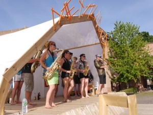 Projekt meyouwedo vor dem Grassimuseum. Zu sehen ist eine Band auf der Bühne, die bei strahlend blauem Himmer an einem Sommernachmittag spielt