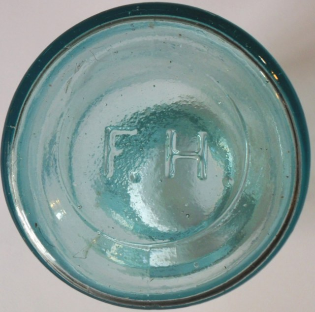 F.H. mark used by Frederick Heitz Glass Works, St. Louis. On base of wax sealer style fruit jar.