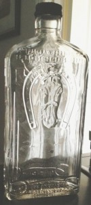 "Spirits bottle with ""Angular"" Glass Containers, Inc. mark on base, as shown in accompanying pic. (Photo courtesy of Michael Aden)."