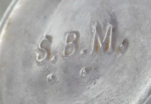 S.B.M. mark on the base of a light amethyst (sun-colored) cylindrical liquor bottle. (Photo courtesy E. Rex)