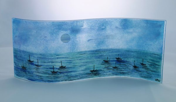 Handpainted fused glass panel with moonlit sea and silhouettes of tiny boats
