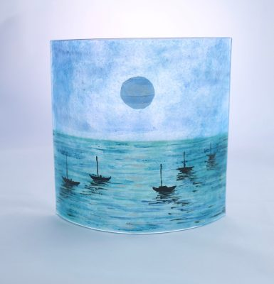 Curved fused glass panel in blues of moonlit sea with silhouettes of little boats