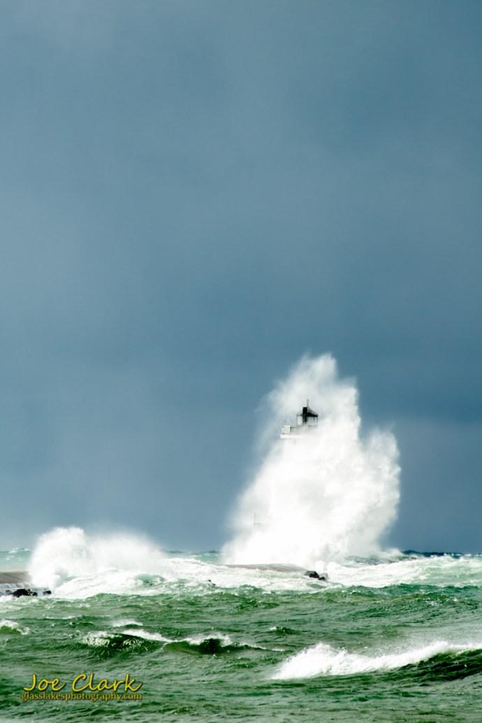 A large wave breaks over the Ludingotn Light, by Joe Clark www.glasslakesphotography.com