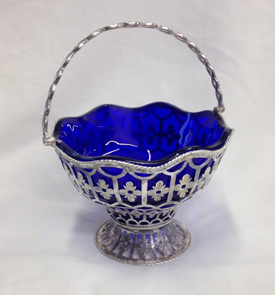 Blue glass liner fitted to a silver sugar basket