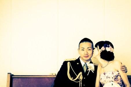 ベンチに座って新郎にキスをする花嫁