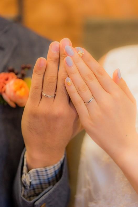 並んで結婚指輪を見せる新郎新婦の手元