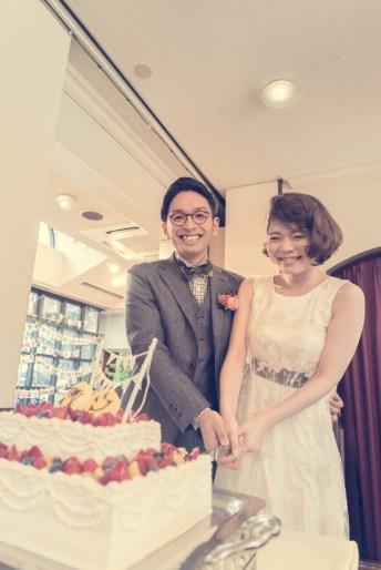ウェディングケーキに入刀して笑顔の新郎新婦