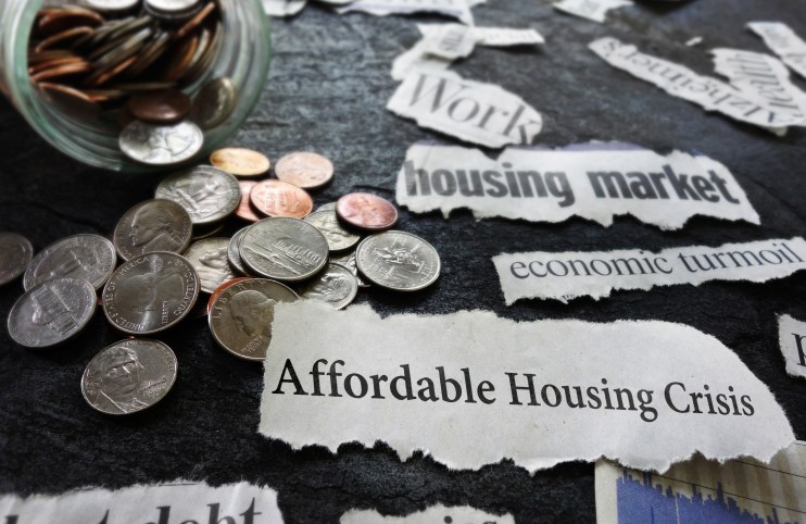 Affordable Housing Crisis newspaper headline and related economic news, with coins