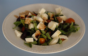 A photo of a caprese salad, including ingredients from our garden.