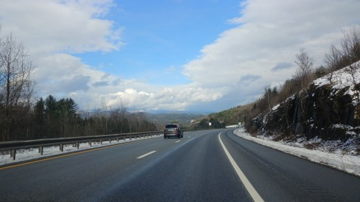 Blue sky and clouds over highway.