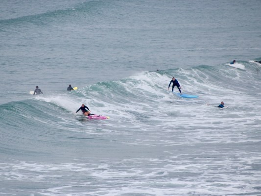 Surfers in the waves at Polzeath