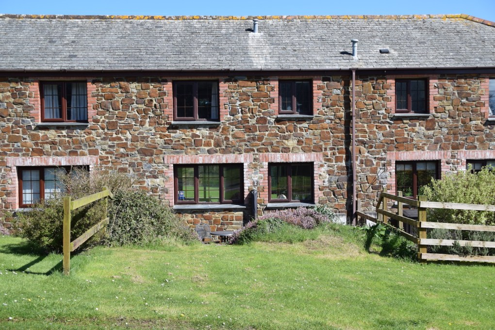 Glen Valley holiday cottage from the back with it's stone and brick walls and slate tiled roof, a small barbecue area and lawn