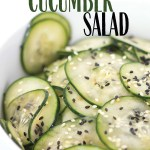 up close shot of sliced cucumbers with sesame seeds in a bowl with title