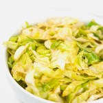 a white bowl of cajun fried cabbage
