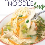 spoonful of homemade chicken noodle soup with sliced lemons, parsley, and rosemary twig