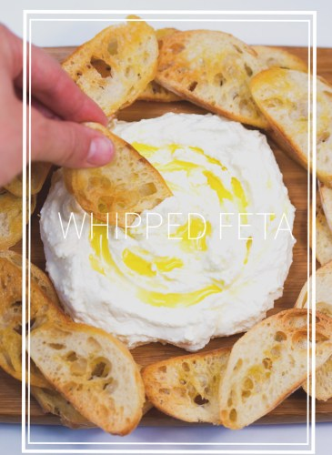 crostinis on a wood cutting board dipping into whipped feta with olive oil drizzle