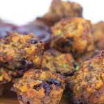 mini muffins with sausage, cranberries and stuffing with parsley on a wood cutting board