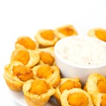 white plate of mini biscuit cups with chicken with a bowl of gravy