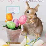 easter table setting with a bunny in the background with a painted clay pot with easter eggs on top with a name tag