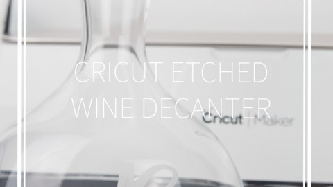 etched glass wine decanter with a cricut maker behind it