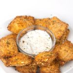 a white plate of air fried toasted spicy ranch ravioli with a bowl of ranch dressing dip