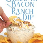 dipping a chip into a glass bowl of easy cheddar bacon ranch dip with cheese and bacon on top with chips around the bowl