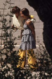 Beverly Hills High School student Erica Farber in a black-and-white gingham, tiered top (dress?) and flared yellow trousers.
