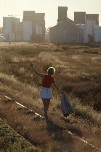 Unidentified student rocks a miniskirt while walking along a disused railroad track, Bird City, Kansas.