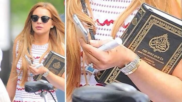 Lindsay Lohan holds the Quran as she leaves her community service