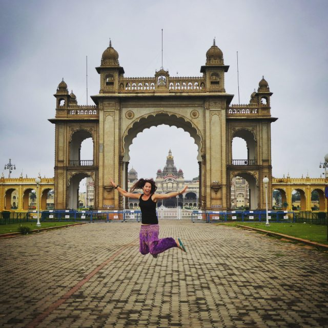 backpacking India jumping outside the elaborate Mysore Palace