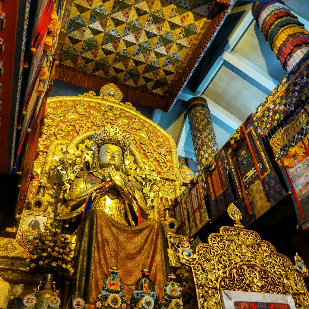 The massive, golden Buddha statue inside the Palpung Sherabling Monastery