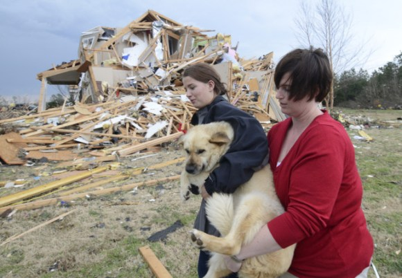Lisa Copeland, right, and Kacie Rose carry a dog to a safe place before a second round of storms approaches Friday, March 2, 2012 in Ooltewah, Tenn. (AP Photo/Chattanooga Times Free Press, Angela Lewis