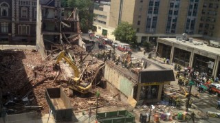The scene as rescuers search the rubble to locate victims. Photo credit: Dino Hazell/Associated Press