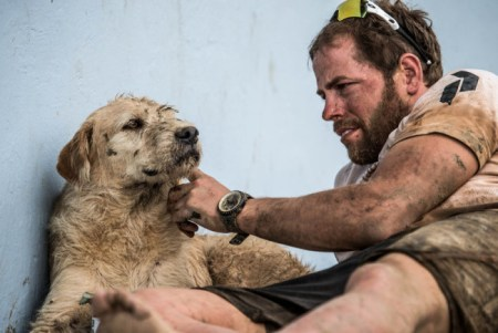 Swedish endurance athlete Mikael Lindnord gives Arthur an affectionate scratch of approval. Photo Credit: Krister Goransson
