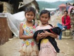 two young girls holding a baby goat after Nepal earthquake