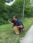 Animal shelter director and shelter dog winston on walk playing pokemon go app